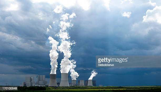Coal-fired power plant and white steam against dark sky.