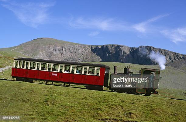A coalfired steam locomotive and carriage ascending the Snowdon Mountain Railway between Hebron Station and Halfway Station The narrow gauge rack and...