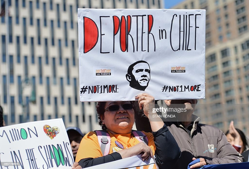A coalition of New York area groups rally to call on Congress to move on immigration reform in Foley Square April 10, 2014 in New York. A woman holds a sign criticizing US President Barack Obama's policy on deportation of undocumented immigrants. AFP PHOTO/Stan HONDA