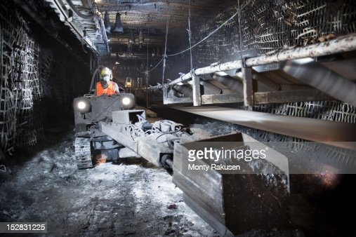 Coalminer operating digger in tunnel of deep mine