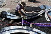 DENVER COAnn Fleming wife of artist Robert Pietruszewski shines part of a titanium kinetic sculpture entitled 'Connections' at Skyline Park on the...