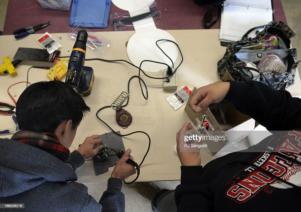 Tim Koh, 18, left, and Zenia Quintana, 18, work on making engines for wind turbines during senior design class at Skyline High School in Longmont, April 11, 2013. The class is part of a program called STEM witch focuses on science, technology, engineering, and math.