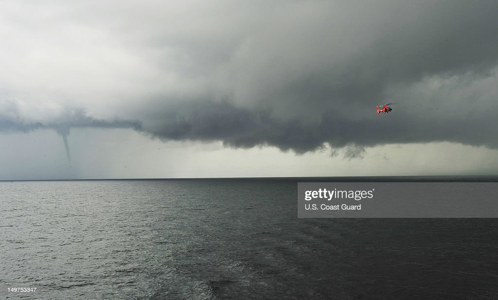 A Coast Guard Air Station Atlantic City MH-65 Dolphin helicopter takes part in deck landing qualifications with the Coast Guard Cutter Diligence as a a water spout forms behind of August 1, 2012 off the coast of Atlantic City, New Jersey.