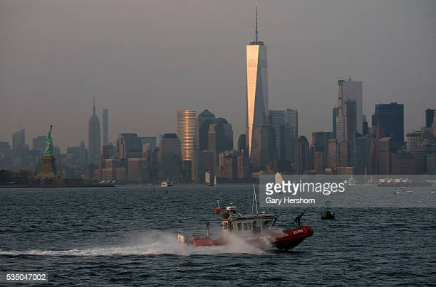 Coast Guard boat passes through the Upper Bay as the sun sets on One World Trade Center and Lower Manhattan on May 26 2016 in New York City