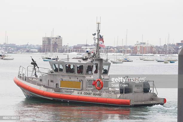 S Coast Guard boat with a machine gun mounted on the front guards the water around the John Joseph Moakley United States Courthouse during the first...