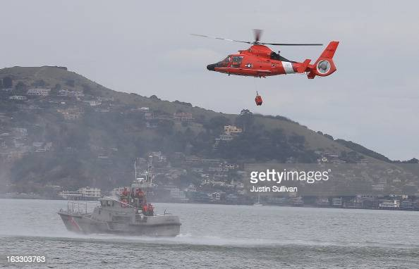 S Coast Guard HH65 Dolphin helicopter participates in a drill with a 47 foot Coast Guard boat on March 7 2013 in San Francisco California The US...