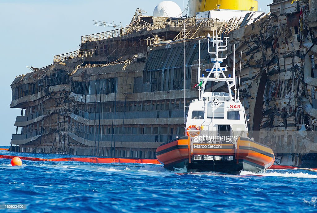 A Coast Guard patrols in front of the severely damaged right side of the Costa Concordia cruise ship on September 18, 2013 in Isola del Giglio, Italy. The vessel, which sank on January 12, 2012, was successfully righted during a painstaking operation yesterday morning. The ship will eventually be towed away and scrapped. It was the first time the procedure, known as parbuckling, had been carried out on a vessel as large as Costa Concordia.