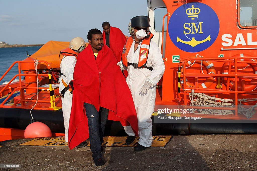 Coast guards from the Spanish Maritime Safety Agency help would-be immigrants to disembark at Tarifa Port after a rescue at high seas on August 30, 2013 in Tarifa, Spain. Members of the Spanish Maritime Safety Agency today rescued seven would-be immigrants when they were crossing the Strait of Gibraltar from Morocco to Spain on a inflatable raft.