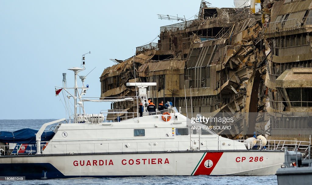 Coast guards patrol near the wreckage of Italy's Costa Concordia cruise ship which begins to emerge from water on September 17, 2013 near the harbour of Giglio Porto Salvage operators in Italy lifted the Costa Concordia cruise ship upright from its watery grave off the island of Giglio in the biggest ever project of its kind. The ship's horn sounded for the first time since the January 13, 2012 tragedy, its sound mixing with applause and cheers in the port in a dramatic climax to the massive salvage operation. Local residents and survivors spoke of an eerie feeling as the ship rose, saying the sight reminded them of the tragedy that claimed 32 lives.