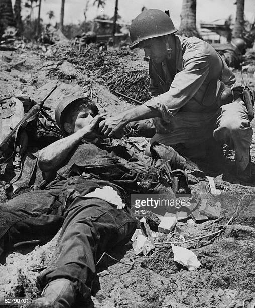 US Coast Guardsman Carol Smith gives a drink of water to injured serviceman Junior F Happel during the Battle of Leyte in the Philippines 20th...