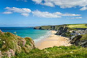 Photo of a Stretch of Coast in Cornwall with a Sandy Beach at the foot of high cliffs.