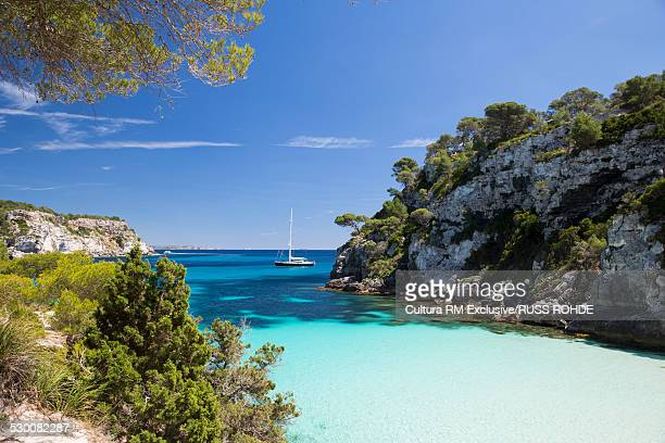 Coastal bay and distant view of yacht, Cala Macarelleta, Menorca, Spain