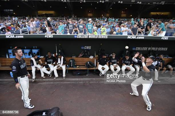 Coastal Carolina University players play a game in the dugout before the start of Game 3 against University of Arizona during the Division I Men's...