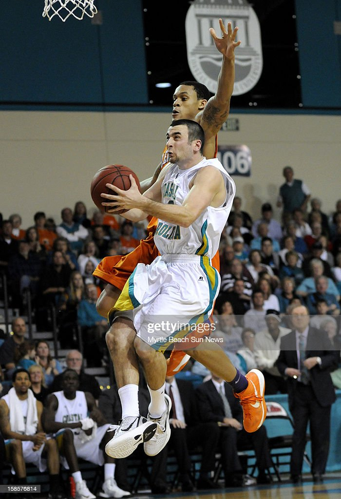 Coastal Carolina's Anthony Raffa goes up for a basket as Clemson's K.J. McDaniels, top, defends during the second half at The HTC Center in Conway, South Carolina, on Wednesday, December 19, 2012. The host Chanticleers won, 69-46.