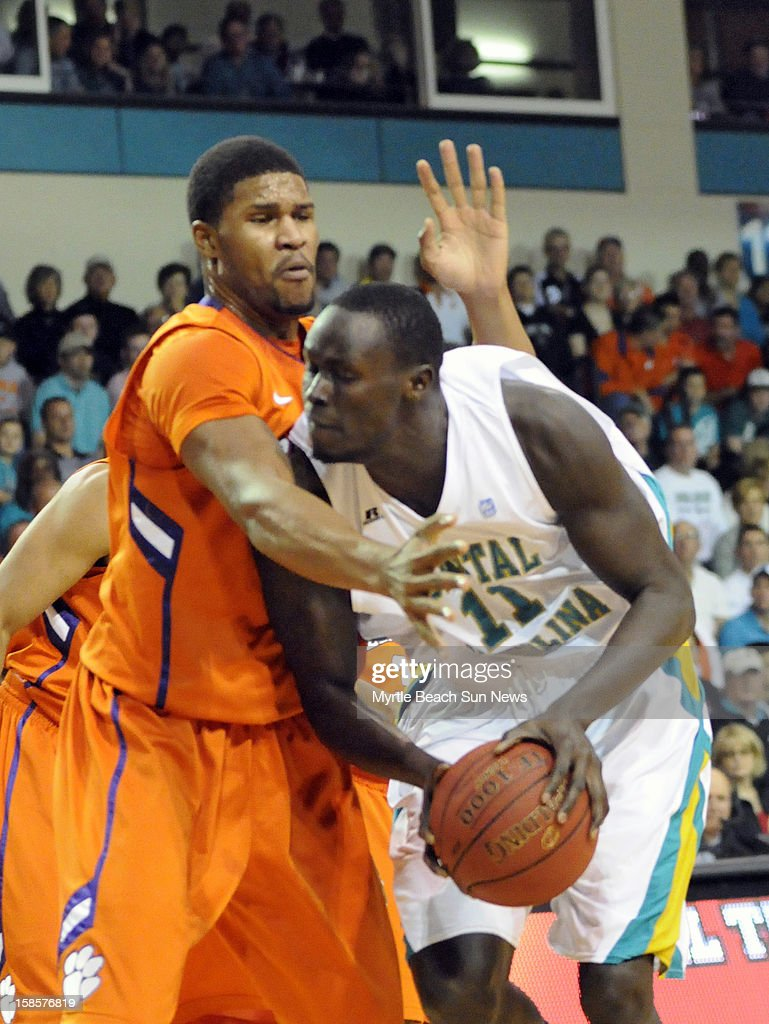 Coastal Carolina's El Hadji Ndieguene (11) drives against Clemson's Devin Booker, left, during the first half at The HTC Center in Conway, South Carolina, on Wednesday, December 19, 2012. The host Chanticleers won, 69-46.
