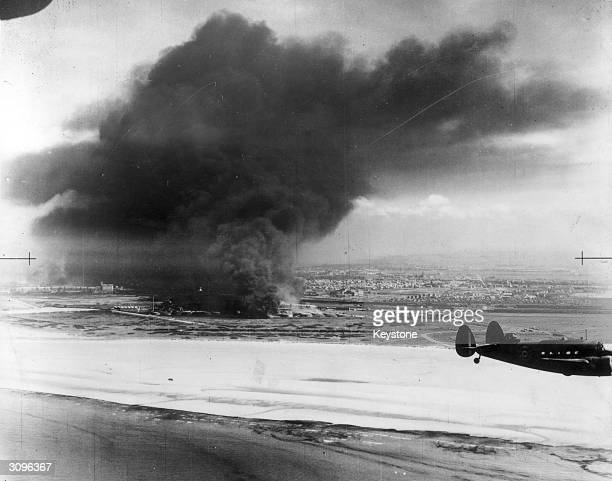 Coastal Command Lockheed Hudson flying past burning oil tanks on Dunkirk beach
