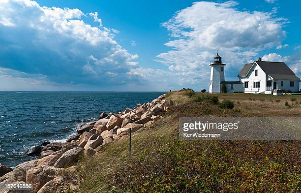 A coastal daytime view of a Cape Cod Lighthouse