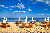 Coastal landscape - Beach umbrellas and loungers on the sandy seashore, the Kavatsi bay near city of Sozopol in Bulgaria
