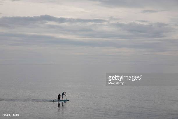 Coastal view of two people paddle boarding on the sea in Seaton in Devon England United Kingdom Seaton is a small seaside town in East Devon on the...