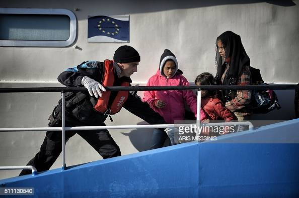 A coastguard helps migrant children disembarking from a Bulgarian FRONTEX ship at the port in Mytilene on the Greek island of Lesbos after crossing...