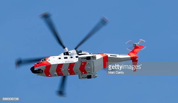 A coastguard rescue helicopter flies overhead as people gather on the beach to take advantage of the fine weather at West Bay on September 1 2016 in...