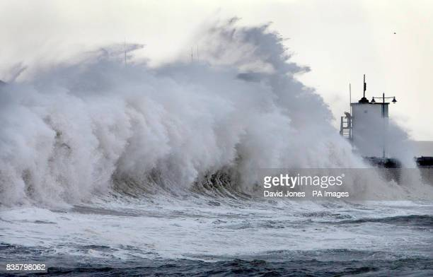 A coastguard shelters behind a tower as waves lash the seafront at Porthcawl Wales