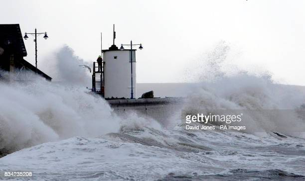 A coastguard watches from a tower as waves lash the seafront at Porthcawl Wales