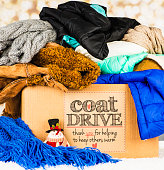 Coat Drive Promotion. Collection box filled with coats and scarves