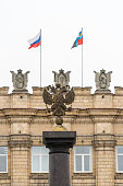 Coat of arms of Russia against the building with flags