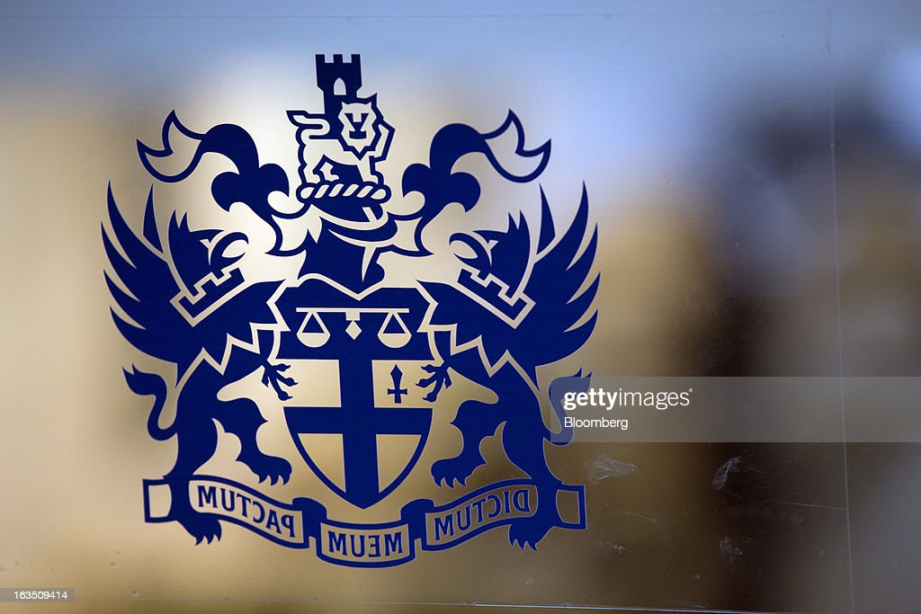 A Coat of Arms sits on a glass wall inside the main entrance of the London Stock Exchange Group Plc's (LSE) headquarters in London, U.K., on Monday, March 11, 2013. European stocks fell from a 4 1/2-year high as Fitch Ratings downgraded Italy and China's retail sales and industrial output missed forecasts. Photographer: Jason Alden/Bloomberg via Getty Images