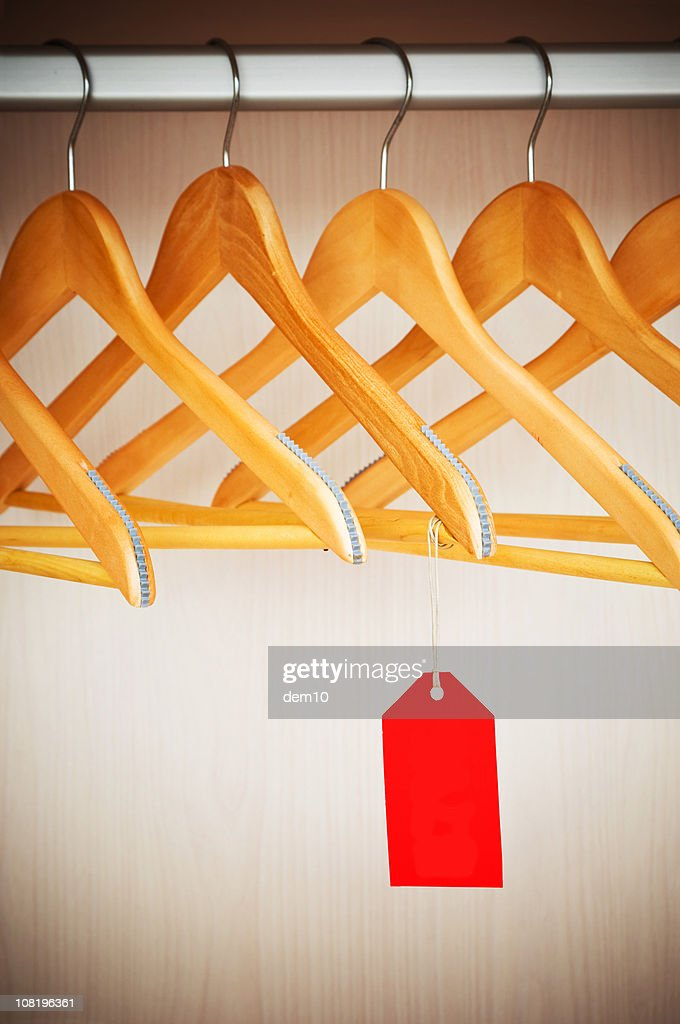 Coathangers on a Clothes Rail with Empty Tag : Stock Photo