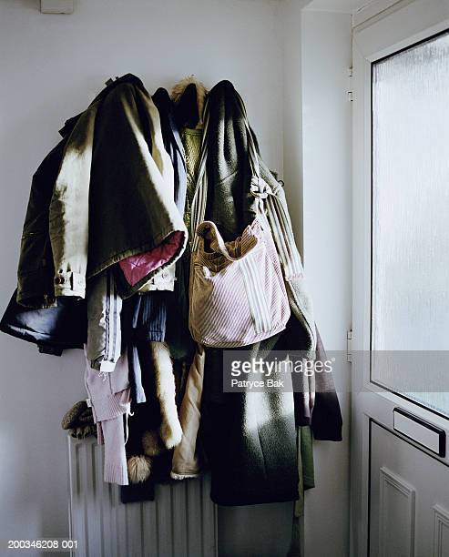 Coats and bags hanging from wall rack by door