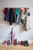 Coats on coat rack with boots