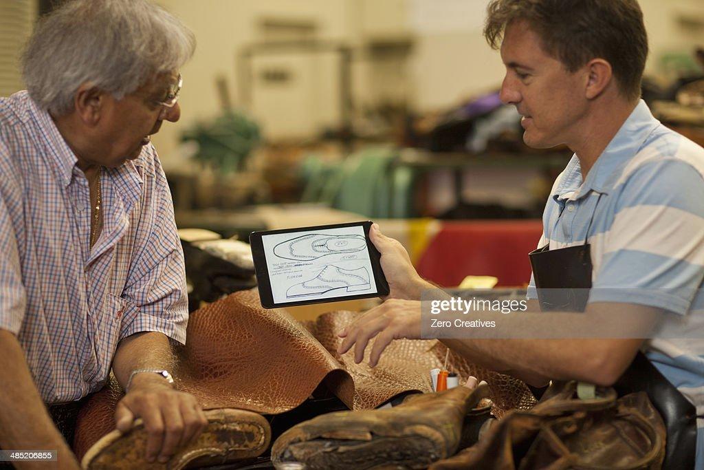 Cobbler and apprentice holding digital tablet