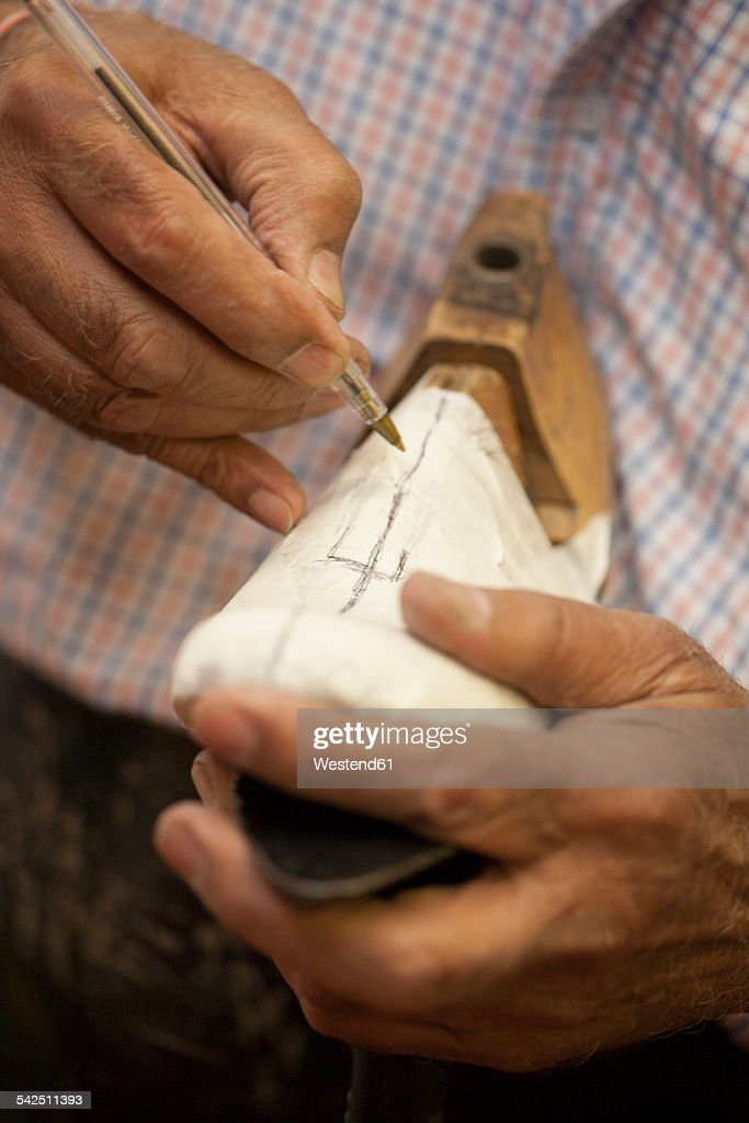 Cobbler marking textile on shoe last with ballpen