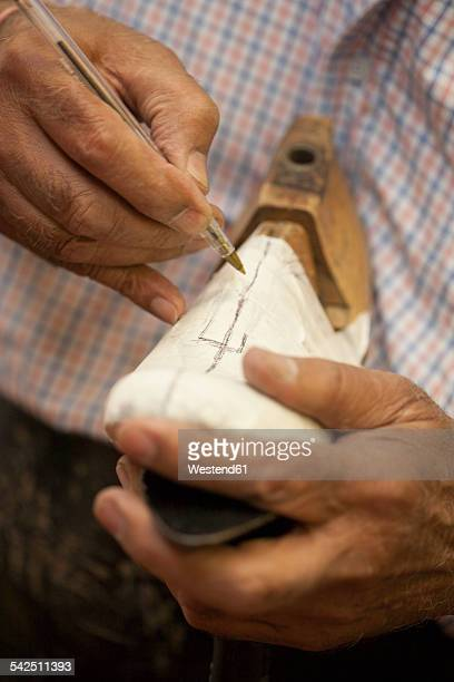 Cobbler marking textile on shoe last with ballpen