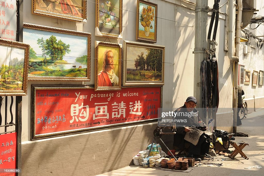 A cobbler works in the sunshine on a street in Shanghai on March 4, 2013. Temperatures rose to 18 degrees celcius in the city as spring gets underway. AFP PHOTO/Peter PARKS