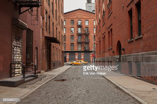 cobblestone Alley in tribeca with taxi passing by