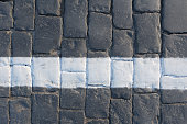 Cobblestone pavement with white line, road concept