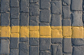 Cobblestone pavement with yellow line, road concept