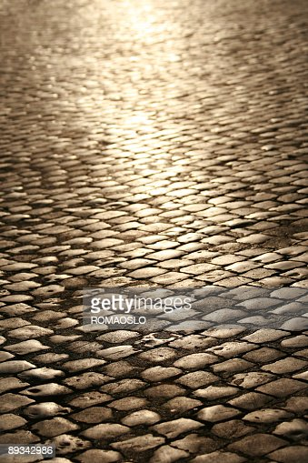 A cobblestone street with a light shining