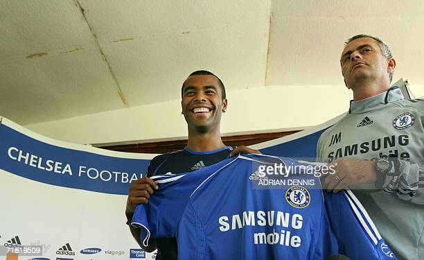 Chelsea's latest football signing Ashley Cole poses with his new shirt alongside Club manager Jose Mourinho during a press conference at the Club's...