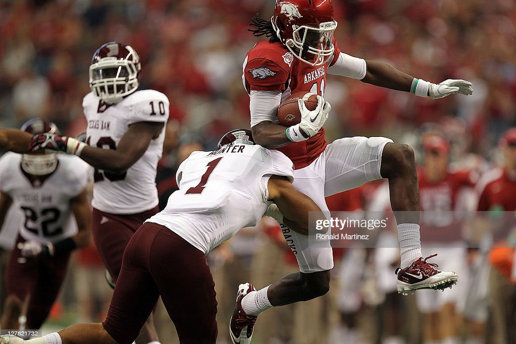 Cobi Hamilton #11 of the Arkansas Razorbacks runs the ball against <a gi-track='captionPersonalityLinkClicked' href=/galleries/search?phrase=Trent+Hunter&family=editorial&specificpeople=202047 ng-click='$event.stopPropagation()'>Trent Hunter</a> #1 of the Texas A&M Aggies at Cowboys Stadium on October 1, 2011 in Arlington, Texas.