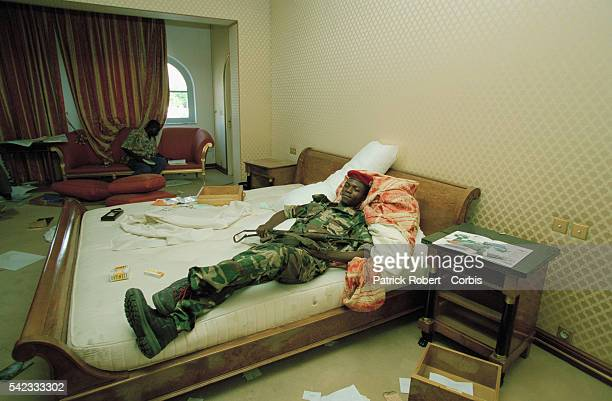 Cobra militiaman stretched out on President Pascal Lissouba's bed in the Presidential Palace The Cobra Militia of General Denis SassouNguesso held by...