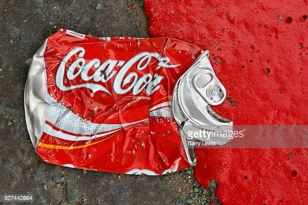A Coca Cola can flattened in the road next to a red route road marking in bright red paint London UK