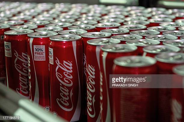 Coca Cola cans are seen on a production line at a new bottling plant in Greater Noida some 50 kms east of New Delhi on August 22 2013 Coca Cola the...