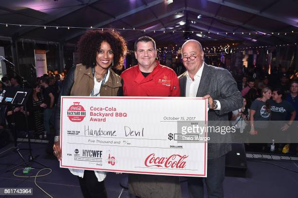 CocaCola Brand Director Jeanine Lewis CocaCola Peoples Choice Award winner Ed Randolph of Handsome Devil and Andrew Zimmern stand onstage at the Food...