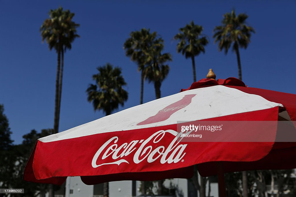 A Coca-Cola branded umbrella stands outside a convenience store in Redondo Beach, California, U.S., on Monday, July 15, 2013. The Coca-Cola Co. is scheduled to release earnings data on July 16. Photographer: Patrick Fallon/Bloomberg via Getty Images