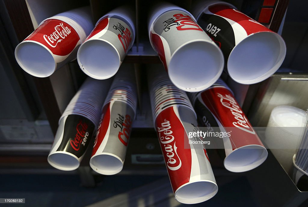 Coca-Cola Co. branded beverage cups sit stored ahead of use behind a sales counter at a Vue Cinema, operated by Vue Entertainment Ltd., at the Westfield Stratford City retail complex in London, U.K., on Tuesday, June 4, 2013. Vue Entertainment, the U.K. cinema chain bought by private equity firm Doughty Hanson & Co., are continuing to expand in Europe, recently acquiring Poland's second-largest cinema chain Multikino. Photographer: Chris Ratcliffe/Bloomberg via Getty Images