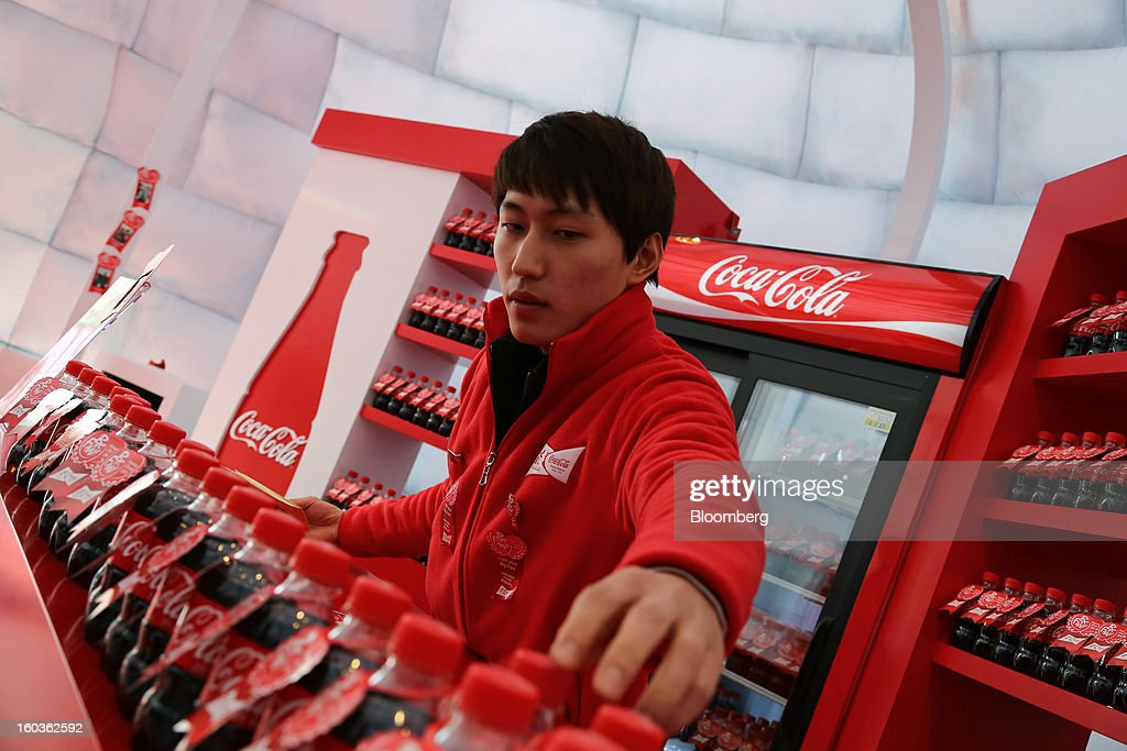 A Coca-Cola Co. event employee arranges bottles of Coca-Cola at the company's promotion booth at the 2013 Pyeongchang Special Olympics Winter Games in Pyeongchang, South Korea, on Wednesday, Jan. 30, 2013. The 2013 Pyeongchang Special Olympics Winter Games takes place from Jan. 29 to Feb 5. Photographer: SeongJoon Cho/Bloomberg via Getty Images